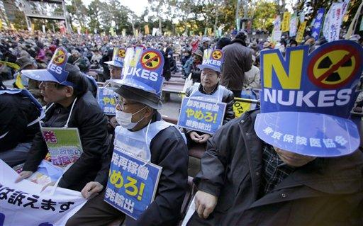2013 оны 12 сарын 22. Цөмийн эсрэг тэмцэгчид Токиод эсэргүүцлийн цуглаан дээр. Парламентийн ордонгийн гадна мянга гаруй хүн цугларч цөмийнэ рчим хүчнээс татгалзаж, 2011 оны Фукушимагийн гамшгийн дараа хаасан АЦС-уудыг дахин ажиллуулахгүй байхыг шаардаж байна. Жагсагчдын зүүсэн плакат нь Цөм хэрэггүй, АЦС бүү ажиллуул гэжээ. (Ассошиэйтид Пресс агентлаг)