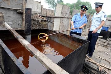 Хүнсний тосны хулгайгаар үйлдвэрлэгчдийг илрүүлсэн цагдаагийн ажилтан хүнсний тосыг шалгаж байгаа нь. 2010 оны 8 сар. Бээжин хот.