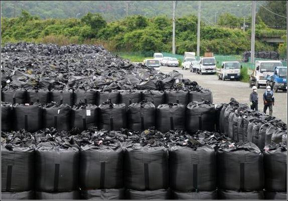 Фукушима мужийн Нараха хотын цацрагт хог хаягдал хадгалах төвийн ажилчид цацрагт бохирдсон шороотой уутны дэргэд зогсож байгаа нь. 20143 оны 6 сарын 13